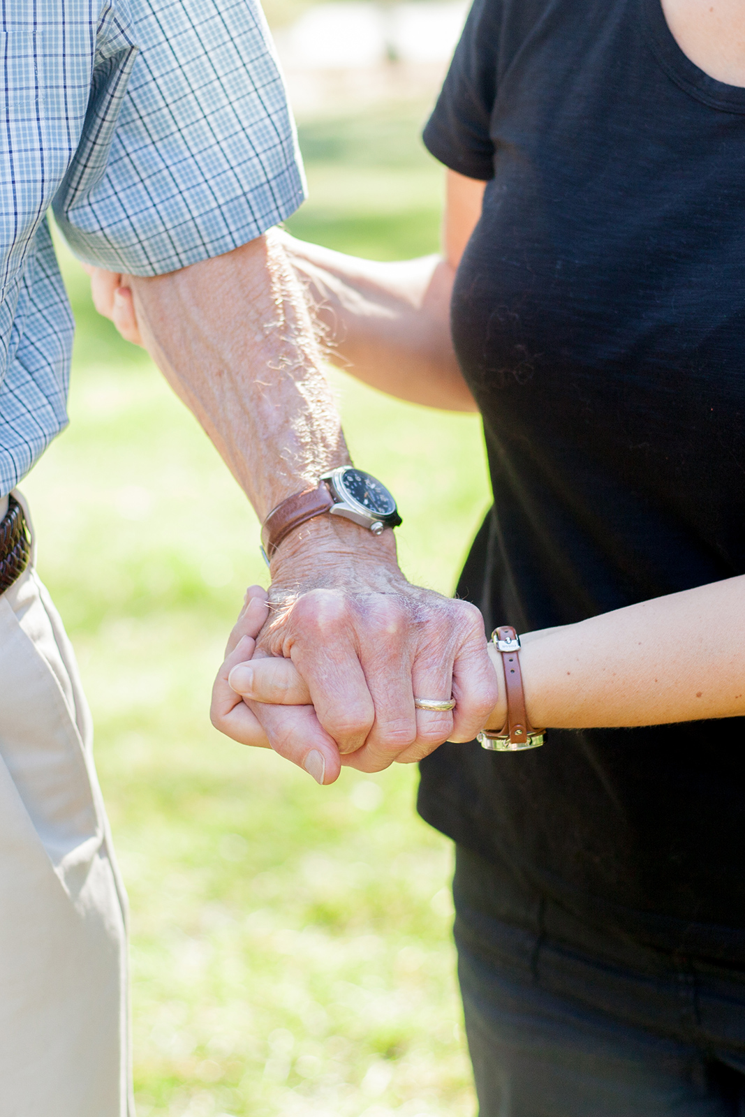 Close crop of an elderly client and a home caregiver holding hands.