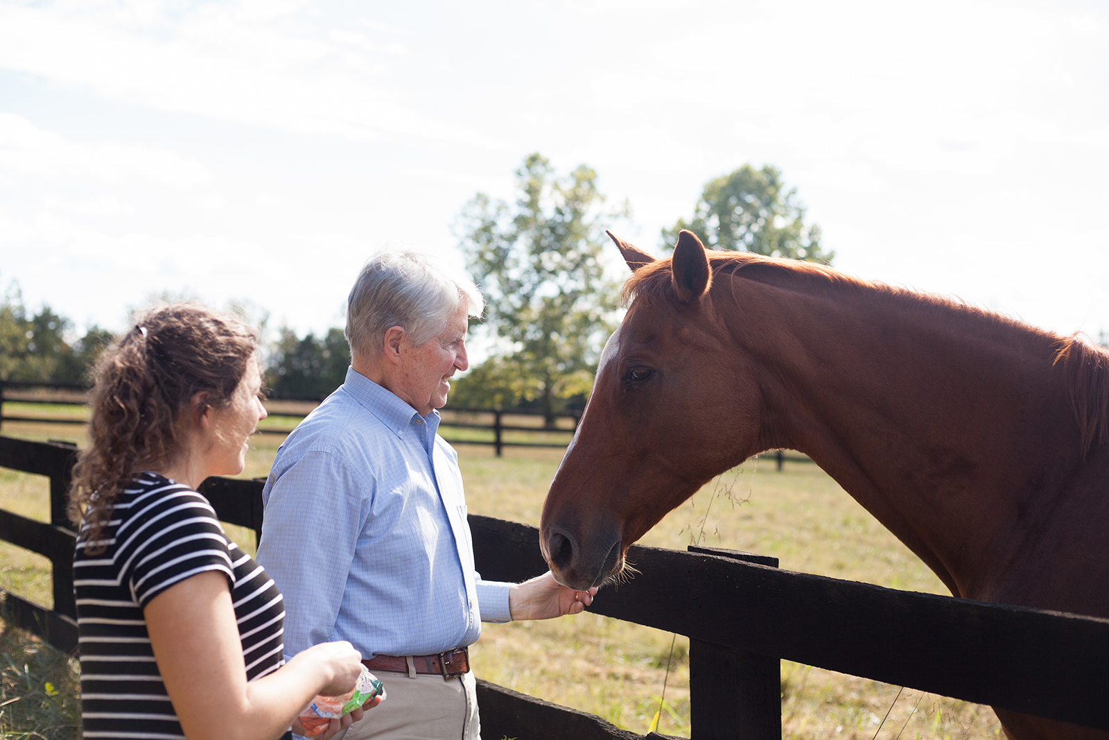 A home caregiver and an elderly man feed carrots to a horse.