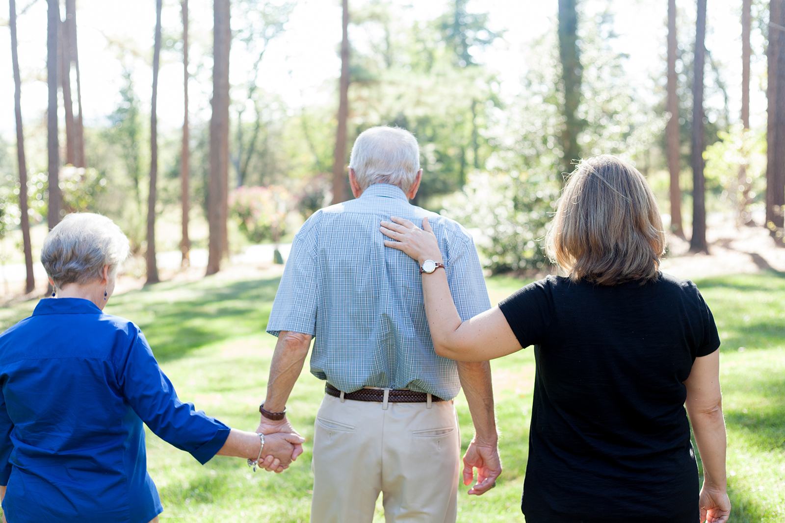 A home caregiver walks toward some trees with an elderly couple.