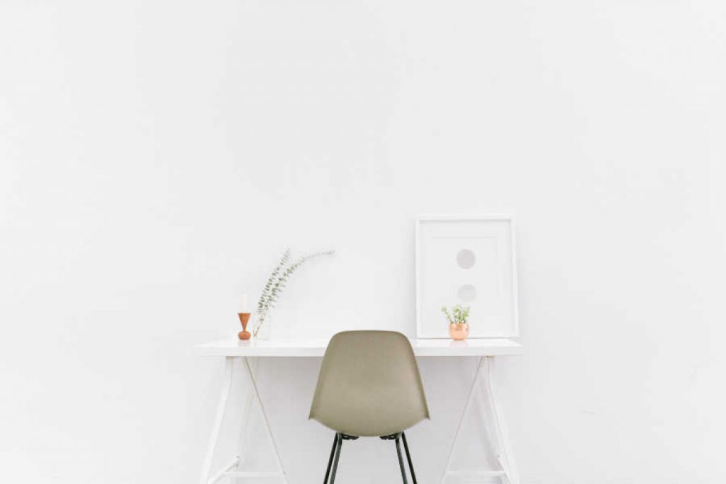 minimal room with white walls, small desk, and green chair