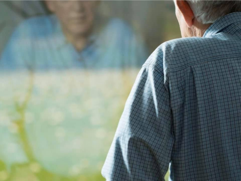 elderly man looking out window depressed