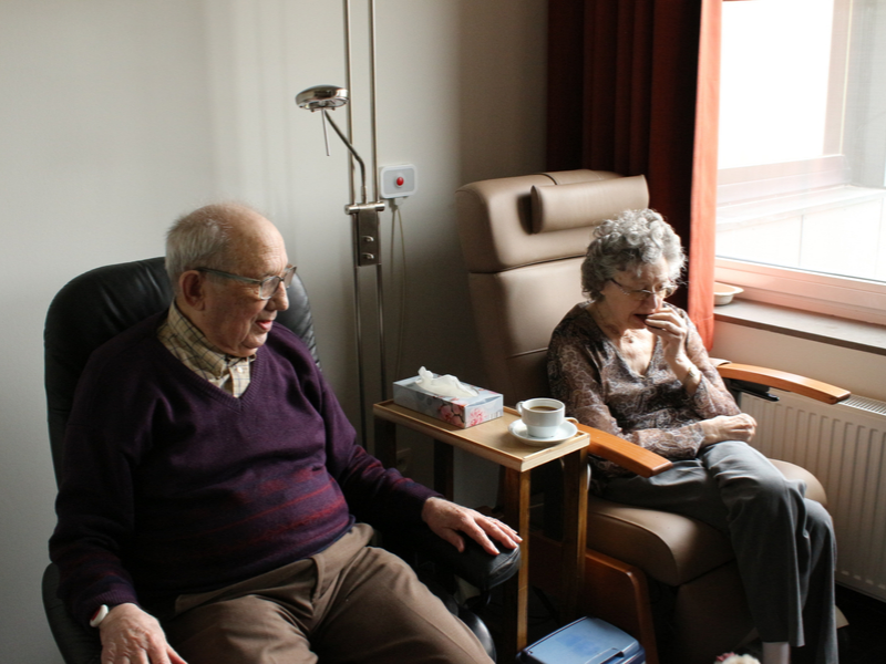 older man and woman sitting in hospital chairs