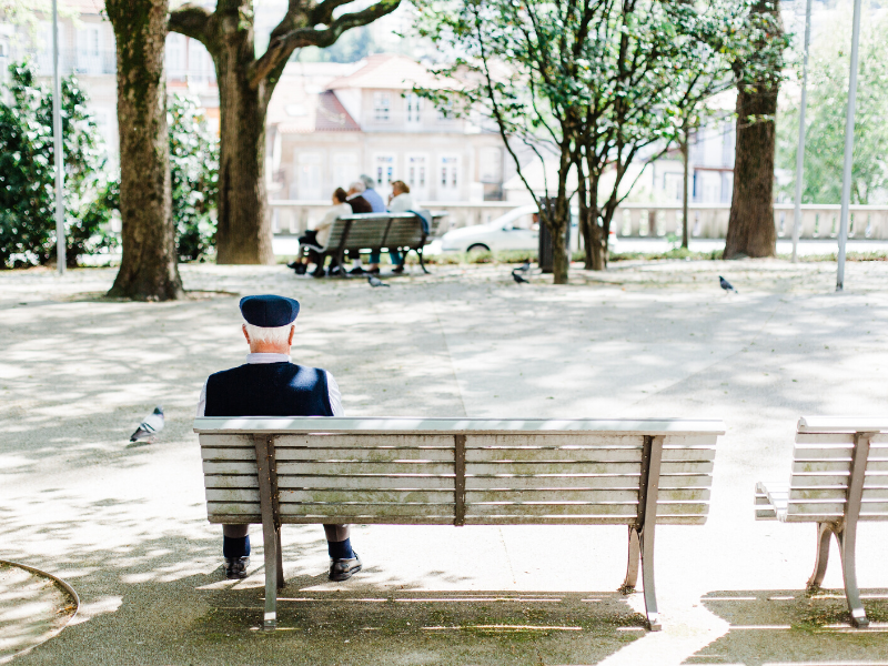 elderly man sitting on bench alone resting