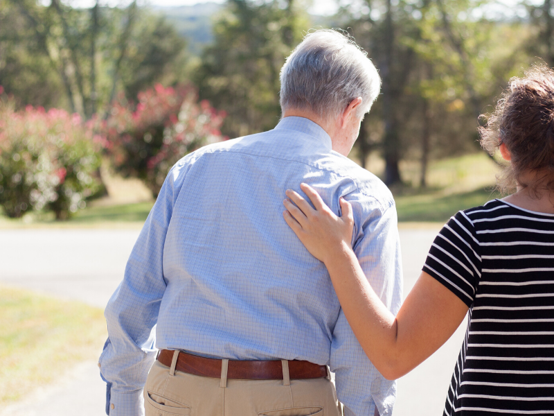 older man walking outside with female caregiver