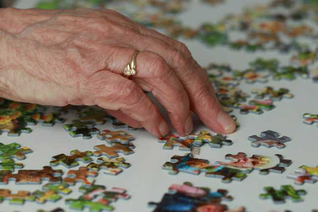 Elderly woman doing a puzzle