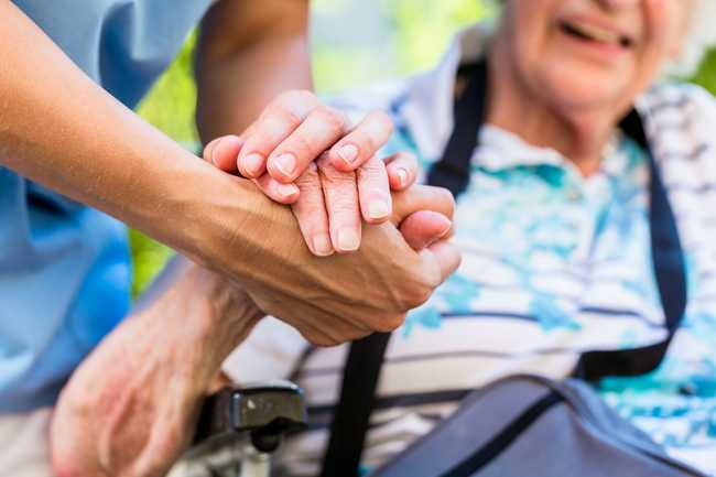 A kind caregiver holding an elderly person's hand