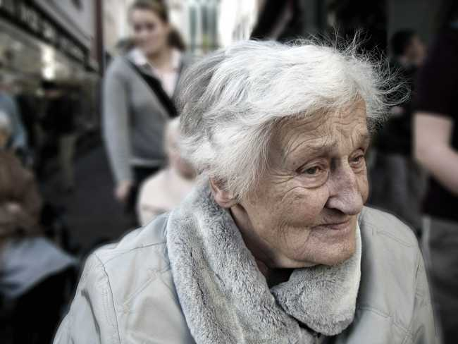 An elderly woman sitting in front of a nursing home