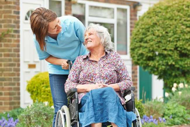 An elderly woman in a wheelchair being pushed by a young woman