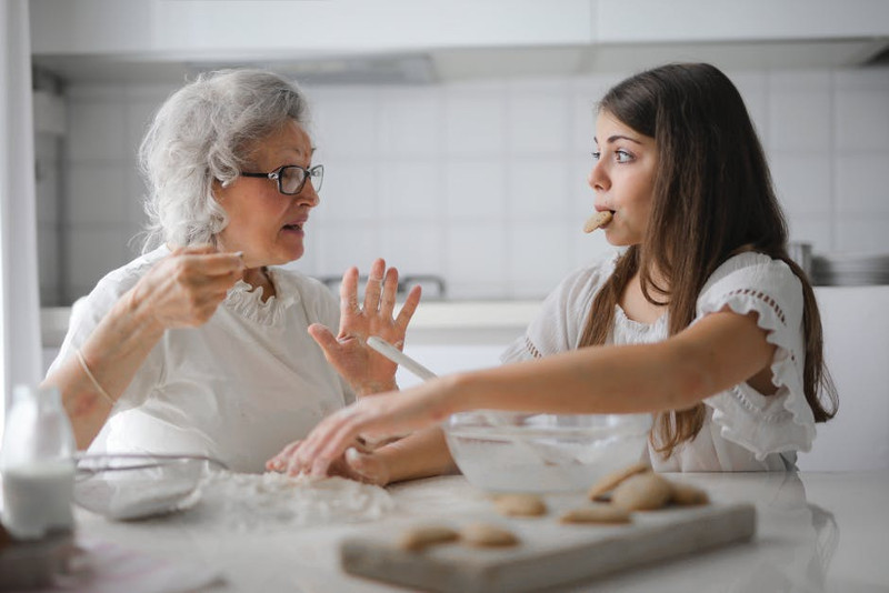 Young lady cooking with her grandmother