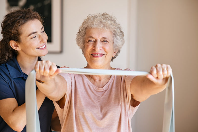 Physiotherapist working with happy senior patient at home