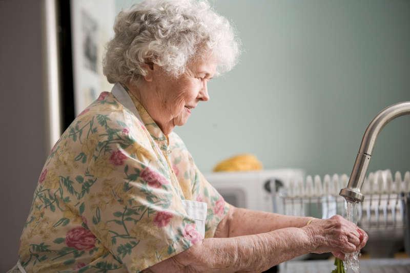 elderly parent washing hands at the sink