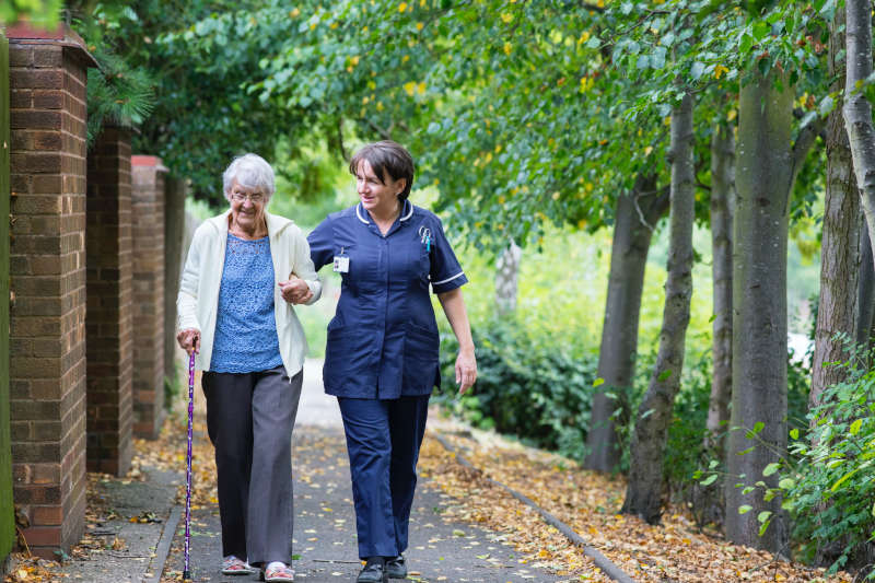 physical therapist walking with an elderly woman