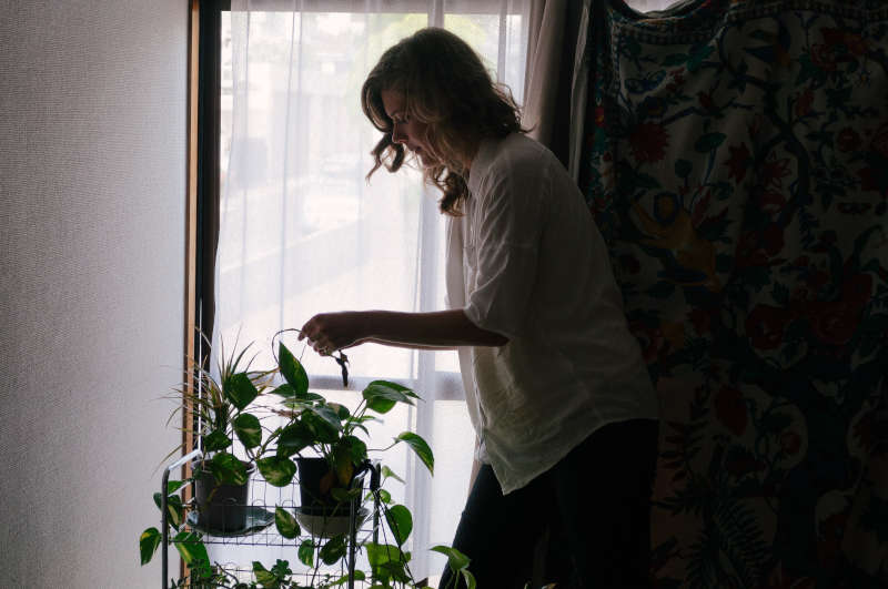 adult child watering plants in her parents home