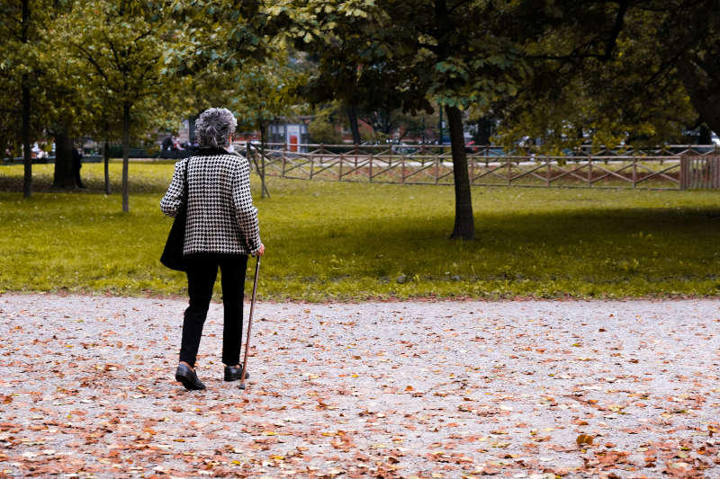 elderly woman walking with a cane in a park