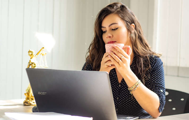 woman sitting at a computer holding a cup of coffee