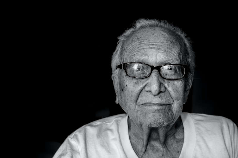 elderly man in a white shirt and black glasses