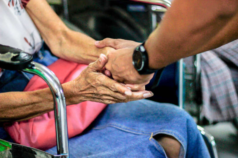 young man holding an elderly womans hands